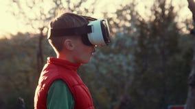 Der Gebrauchsvirtuellen realität des kleinen Jungen Kopfhörersturzhelm stock video