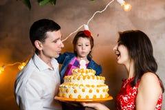 Der Geburtstag der Themafamilienurlaub-Kinder und Kerzen auf großem Kuchen heraus durchbrennen junge Leute der dreiköpfigen Famil Stockfoto