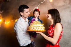 Der Geburtstag der Themafamilienurlaub-Kinder und Kerzen auf großem Kuchen heraus durchbrennen junge Leute der dreiköpfigen Famil Stockbilder