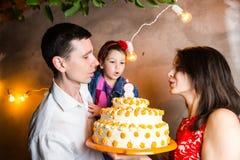 Der Geburtstag der Themafamilienurlaub-Kinder und Kerzen auf großem Kuchen heraus durchbrennen junge Leute der dreiköpfigen Famil Lizenzfreies Stockfoto