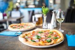 Der gediente Abendtisch mit Pizza in der Pizzeria oder im Restaurant Lizenzfreies Stockbild