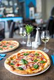 Der gediente Abendtisch mit Pizza in der Pizzeria oder im Restaurant Stockfoto