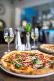 Der gediente Abendtisch mit Pizza in der Pizzeria oder im Restaurant Stockfotografie