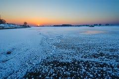Der gefrorene Flusssonnenaufgang Stockfotos
