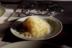Der geriebene Käse auf bunter Platte mit Schatten und Sonne strahlt aus Lizenzfreie Stockbilder