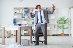 Der Geschäftsmann, der den Spaß macht eine Pause im Büro bei der Arbeit hat Stockfoto