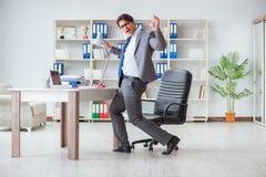 Der Geschäftsmann, der den Spaß macht eine Pause im Büro bei der Arbeit hat Stockfotografie