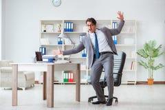 Der Geschäftsmann, der den Spaß macht eine Pause im Büro bei der Arbeit hat Lizenzfreie Stockfotografie