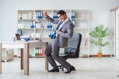Der Geschäftsmann, der den Spaß macht eine Pause im Büro bei der Arbeit hat Lizenzfreie Stockbilder