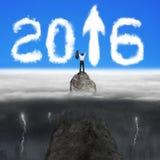 Der Geschäftsmann, der auf Bergspitze für Pfeilzeichen 2016 zujubelt, bewölkt sich Stockfotos