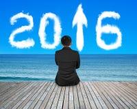 Der Geschäftsmann, der auf Boden mit Pfeil 2016 sitzt, bewölkt Himmelmeer Lizenzfreie Stockbilder