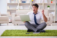 Der Geschäftsmann, der auf dem Boden im Büro sitzt Lizenzfreies Stockfoto