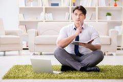 Der Geschäftsmann, der auf dem Boden im Büro sitzt Stockbilder