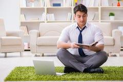 Der Geschäftsmann, der auf dem Boden im Büro sitzt Stockfotos