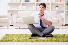 Der Geschäftsmann, der auf dem Boden im Büro sitzt Stockfoto