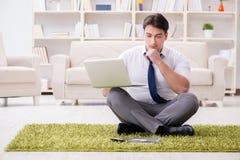Der Geschäftsmann, der auf dem Boden im Büro sitzt Lizenzfreies Stockbild