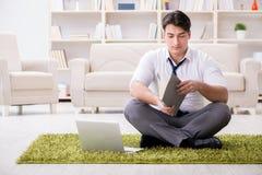 Der Geschäftsmann, der auf dem Boden im Büro sitzt Lizenzfreie Stockfotos