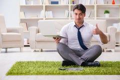 Der Geschäftsmann, der auf dem Boden im Büro sitzt Stockfotografie