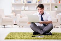 Der Geschäftsmann, der auf dem Boden im Büro sitzt Stockbild