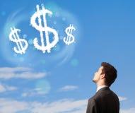 Der Geschäftsmann, der auf Dollarzeichen zeigt, bewölkt sich auf blauem Himmel Lizenzfreie Stockfotos