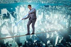 Der Geschäftsmann, der das Drahtseil geht in Risikokonzept tut Stockfoto