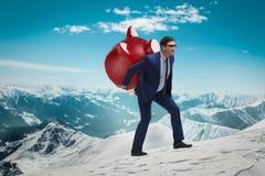 Der Geschäftsmann, der das piggybank mit Einsparungen trägt Lizenzfreie Stockbilder
