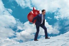 Der Geschäftsmann, der das piggybank mit Einsparungen trägt Lizenzfreie Stockfotografie