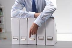 Der Geschäftsmann, der Dateien auf Mappe hält, legt Hintergrund beiseite Lizenzfreies Stockfoto