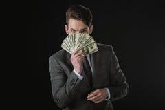 Der Geschäftsmann, der Dollarbanknoten hält, lockern lokalisiert auf Schwarzem auf Lizenzfreie Stockfotos