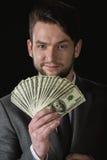 Der Geschäftsmann, der Dollarbanknoten hält, lockern lokalisiert auf Schwarzem auf Stockbilder