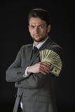 Der Geschäftsmann, der Dollarbanknoten hält, lockern lokalisiert auf Schwarzem auf Stockfotografie
