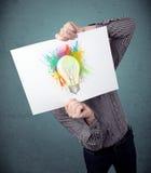 Der Geschäftsmann, der eine Pappe mit Farbe hält, spritzt und lightbul Lizenzfreies Stockfoto