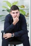Der Geschäftsmann, der in einem Stuhl sitzt, sorgte sich um zu viel Arbeit Stockfoto