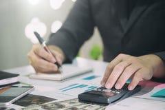 Der Geschäftsmann, der Finanzen berechnen tut an, die Analyse, die mit f arbeitet Stockfotos