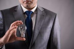 Der Geschäftsmann, der Glühlampe im Kreativitätskonzept hält Stockfotos