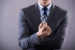 Der Geschäftsmann, der Glühlampe im Kreativitätskonzept hält Lizenzfreie Stockfotos