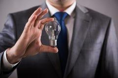 Der Geschäftsmann, der Glühlampe im Kreativitätskonzept hält Lizenzfreies Stockbild