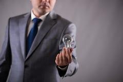 Der Geschäftsmann, der Glühlampe im Kreativitätskonzept hält Lizenzfreie Stockfotografie