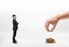Der Geschäftsmann, der groß betrachtet, bemannt die Hand, die Stapel von den goldenen Münzen macht, die auf weißem Hintergrund lo Stockfotografie