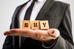 Der Geschäftsmann, der hölzernes Alphabet hält, blockiert das schüchterne Ablesen Stockfotografie