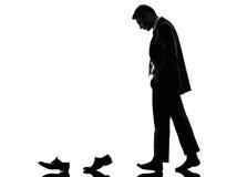 Der Geschäftsmann, der hinter seine Schuhe geht, kleidet Schattenbild lizenzfreies stockbild