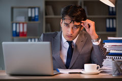 Der Geschäftsmann, der im Büro für Überstunden bleibt Stockfotos