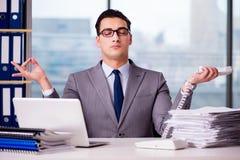 Der Geschäftsmann, der im Büro meditiert stockbilder