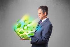 Der Geschäftsmann, der Laptop mit hält, bereiten und Klima-symbo auf Stockfotografie