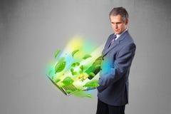 Der Geschäftsmann, der Laptop mit hält, bereiten und Klima-symbo auf Stockfotos