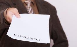 Der Geschäftsmann, der leeres Papier mit gibt, unterzeichnen Vertrag Stockfoto