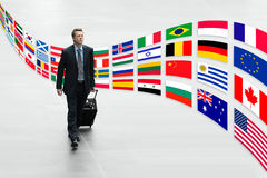 Der Geschäftsmann, der mit internationalen Flaggen der Laufkatze reist, lösen Konzept aus Stockfotos