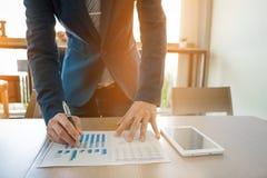 Der Geschäftsmann, der mit Tablette arbeiten und das Diagramm stellen Daten bezüglich des Holzes grafisch dar Lizenzfreie Stockfotografie