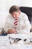 Der Geschäftsmann, der oben mit gebunden wird, fangen das Büro ein. Arbeit ohne Ende Lizenzfreies Stockbild
