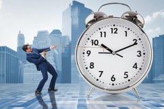 Der Geschäftsmann, der Uhr im Zeitmanagementkonzept zieht Lizenzfreies Stockbild